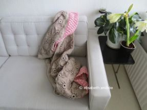 beige pink blanket on couch