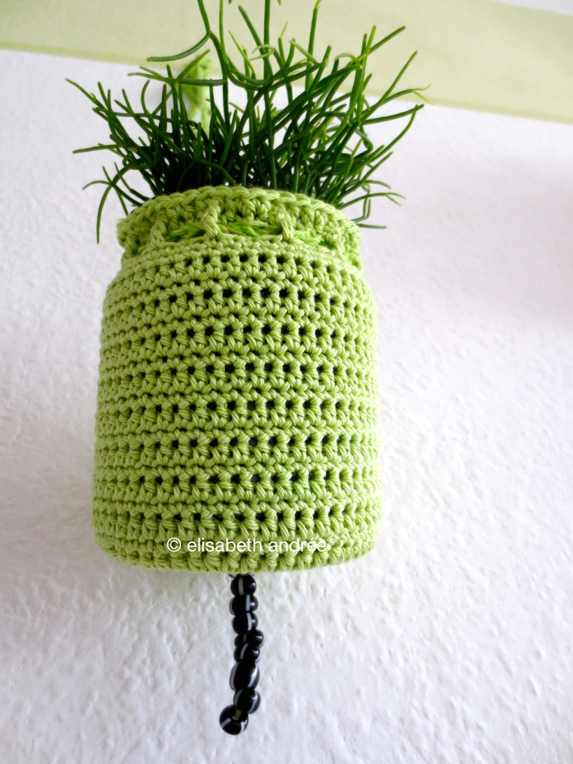 green crochet planthanger with black and white beads