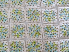 small squares of variegated yarn with off white edges