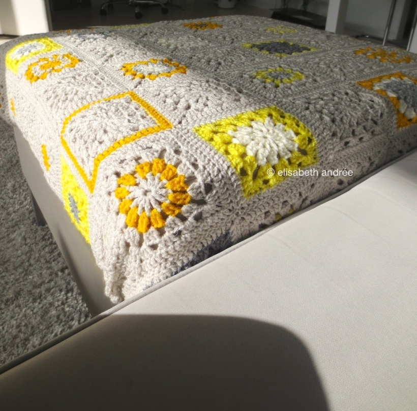 small square crochet blanket on footstool by elisabeth andrée