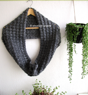crochet charcoal cowl on hanger and plant