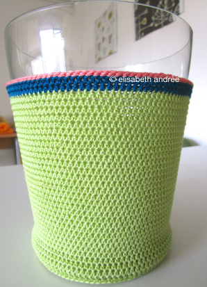 crochet vase cover in soft green with teal and coral top edge