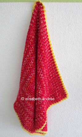 small blanket of red variegated yarn with yellow edge